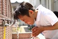 校庭で顔を洗う少年