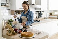 タブレットを見て料理する女性