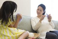 編み物をする妊婦の母親と娘