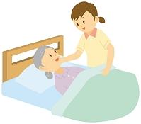 介護ベッドに寝ている老人女性と女性介護士