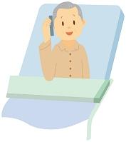 介護ベッドの上で携帯電話で話す老人日本人男性