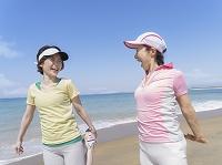 海辺でストレッチをする母と娘