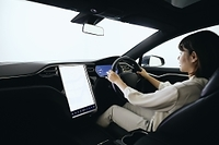 自動運転の車を運転する日本人女性