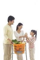 ショッピングカートで買い物をする両親と女の子