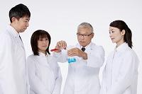 試験管とフラスコで実験する白衣の研究者男女