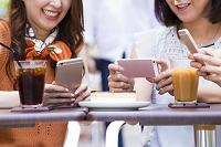オープンカフェでスマートフォンを操作する日本人女性