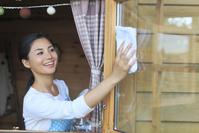 家の窓ガラスを磨く日本人女性