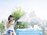 シャワーで水まきする日本人親子