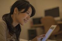 タブレットPCを操作する日本人の若い女性