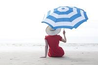 砂浜でパラソルを持った女性