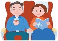飛行機の座席で寛ぐ中高年夫婦