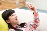 寝転んでスマートフォンを見る日本人の女の子