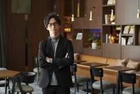 カフェで腕組みをする日本人男性