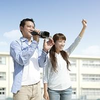 ビデオカメラを持って笑う夫婦