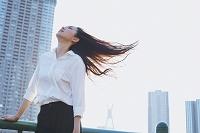 風に髪をなびかせる日本人ビジネスウーマン