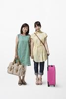 鞄とスーツケースを持つ母と娘