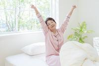 ベッドに座って伸びをするパジャマ姿のシニア日本人女性