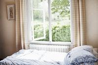 窓の開いた爽やかな寝室
