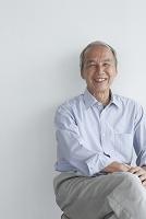 椅子に座る笑顔のシニアの日本人男性