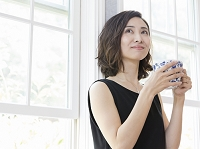 窓辺でティーカップを持つ日本人女性