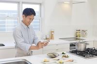 朝食を作りスマートフォンで撮影する中年男性