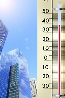 高温を表示する温度計と都会の街並み
