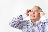 こめかみに手をあてるシニア日本人男性