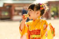 糸電話で遊ぶ晴れ着の女の子