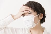 額に手を置くマスクをした女性
