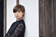 古民家の壁に寄りかかり横を見てる日本人女性