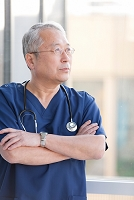 腕組みをして窓の外を見る医師