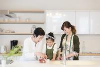 キッチンでイチゴを洗う孫と母と祖母