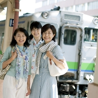 駅のホームで微笑む親子と中年日本人女性