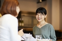 レストランで友人と話す日本人女性