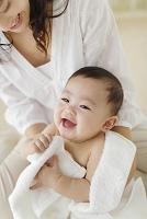 風呂上りの裸の赤ちゃんをバスタオルで拭くお母さん