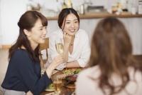 ホームパーティーで友人と話す若い女性