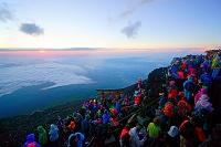 山梨県 富士山頂上からのご来光と鳥居と登山者