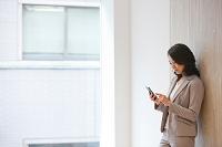 スマートフォンを操作する日本人ビジネスウーマン