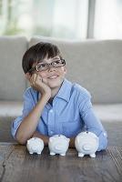 眼鏡をかけた男の子とブタの貯金箱