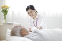 ベッドに横たわるシニアと笑顔の日本人女性介護士