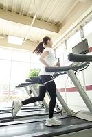 ランニングマシンで走る女性