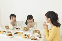 食卓でママと一緒にいただきますをする子供達