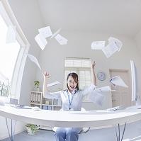 書類を投げるビジネスウーマン