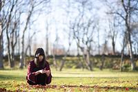 落ち葉を拾う日本人女性