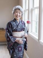 花を持つ着物のシニア日本人女性