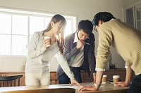 ドリンクカップを手に持ちミーティングをする20代男女3人