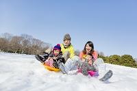 雪の公園でソリ遊びをする日本人家族