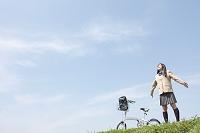 自転車と腕を広げる女子高校生