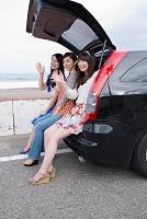 海岸で車にもたれかかる若い女性