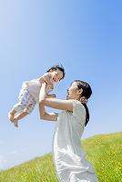 野花の咲く丘で娘を抱き上げる母親